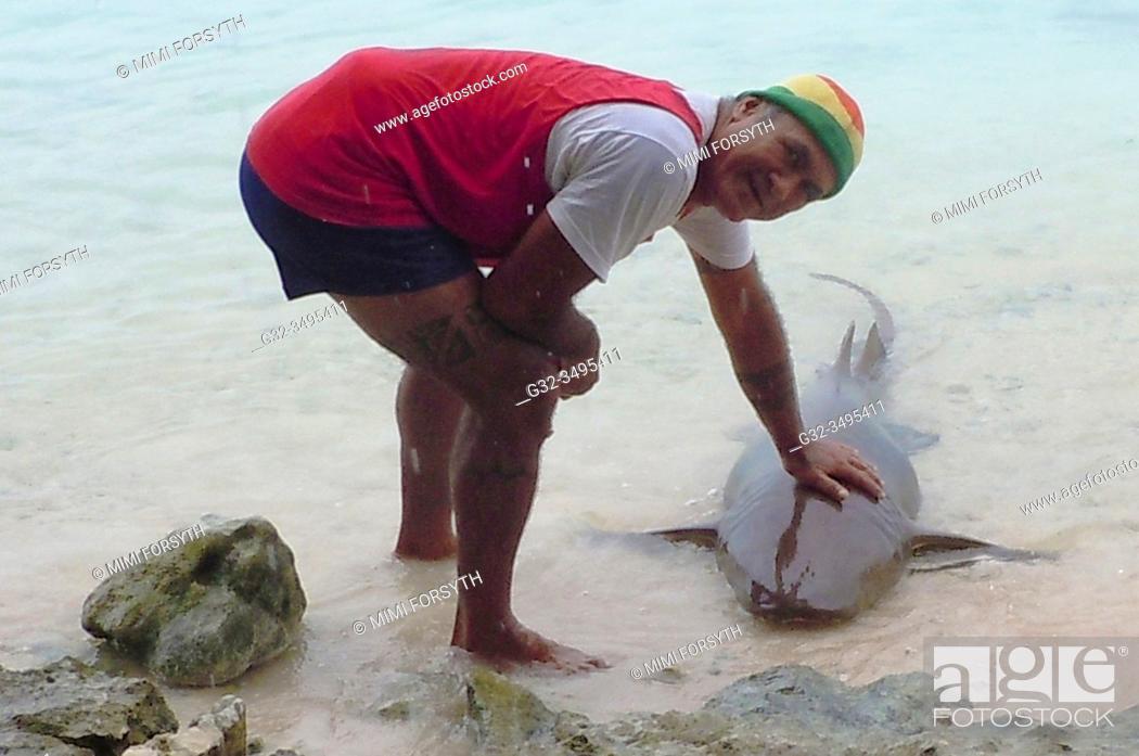 Stock Photo: man with pet shark, Fakarava, Tuamotus, French Polynesia.