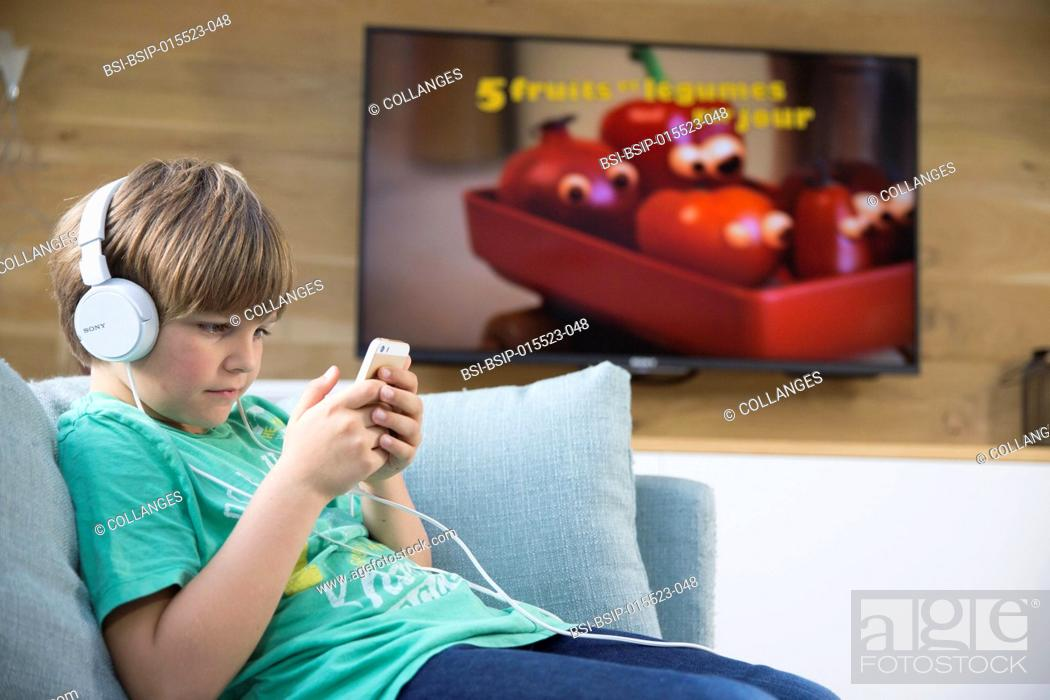 Stock Photo: A child playing with a smartphone next to the television.