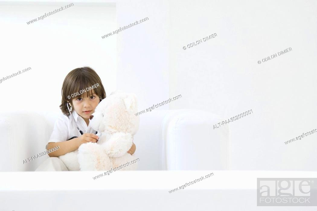 Stock Photo: Little boy playing doctor with teddy bear, using stethoscope.