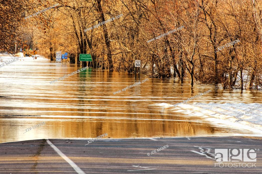 Stock Photo: Flood waters of the Minnesota River flow over highway 101 north of downtown Shakopee, Minnesota in March 2010.