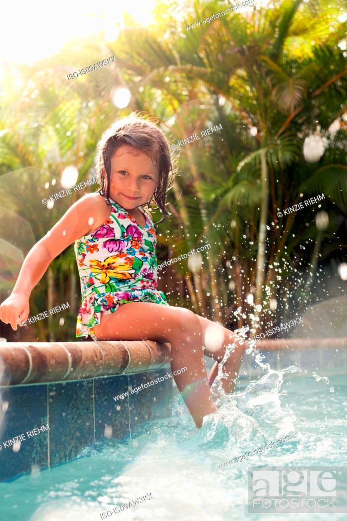 Stock Photo: Girl wearing swimming costume sitting on sunlit poolside splashing.