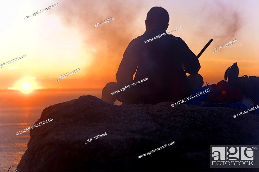 Stock Photo: pilgrim enjoying a sunset in Cape Finisterre and burning the clothes used during the peregrination to Santiago de Compostela  Finisterre Coruña province Spain.