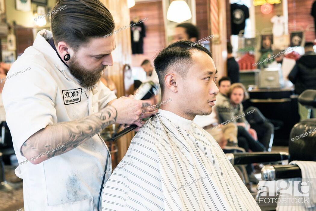 rotterdam, netherlands. barber store schorem. barber helping his