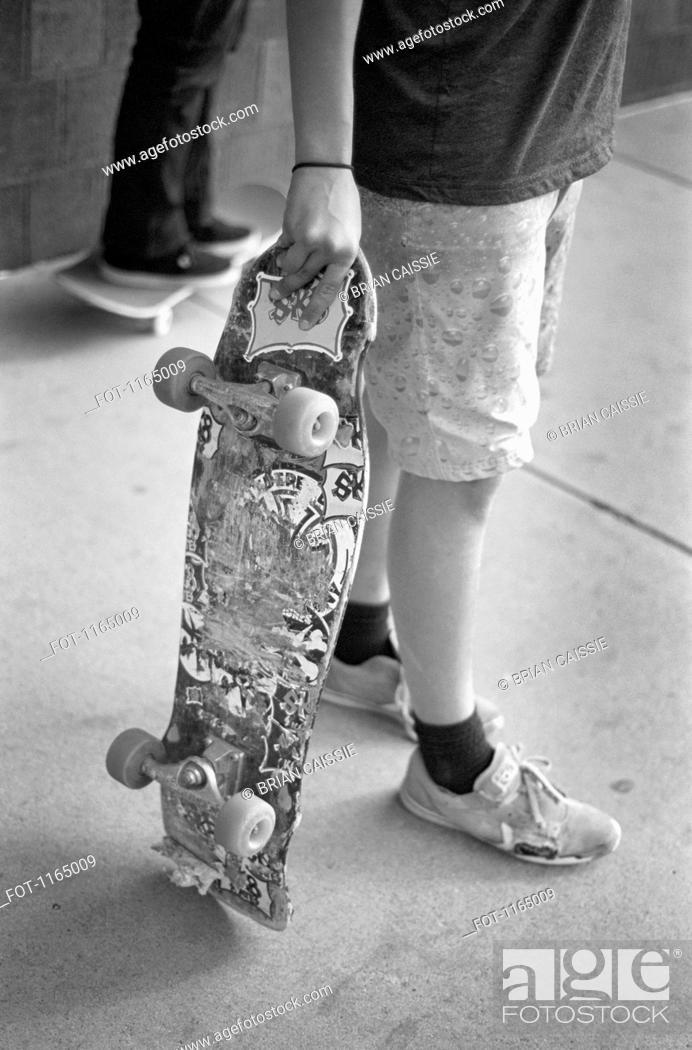 Stock Photo: A man holding a skateboard, waist down.