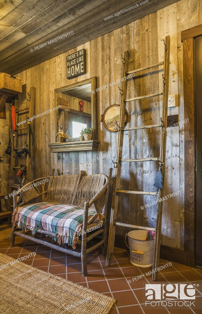 Stock Photo: Mudroom with reclaimed barn wood walls, terracotta ceramic floor tiles, rustic wooden loveseat and ladders inside a LEED certified Country home.