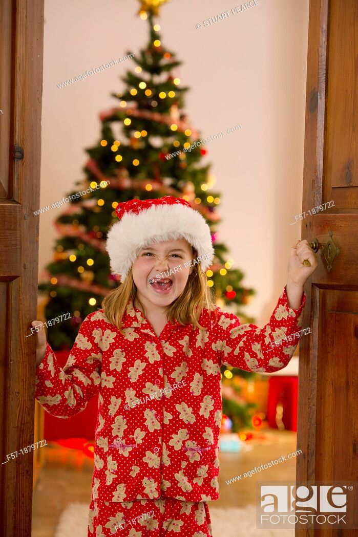 Stock Photo: Young girl opening the living room doors at Christmas time.