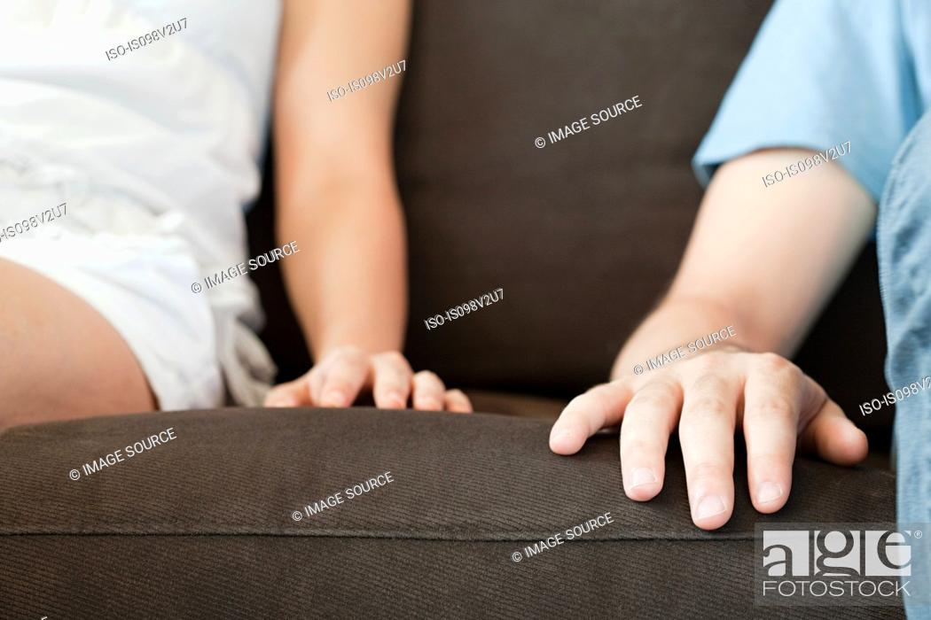 Stock Photo: Close up of hands of couple on sofa.