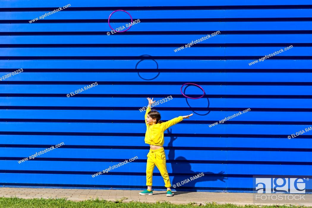 Stock Photo: Little girl wearing yellow tracksuit throwings gymnastic rings in the air in front of blue background.