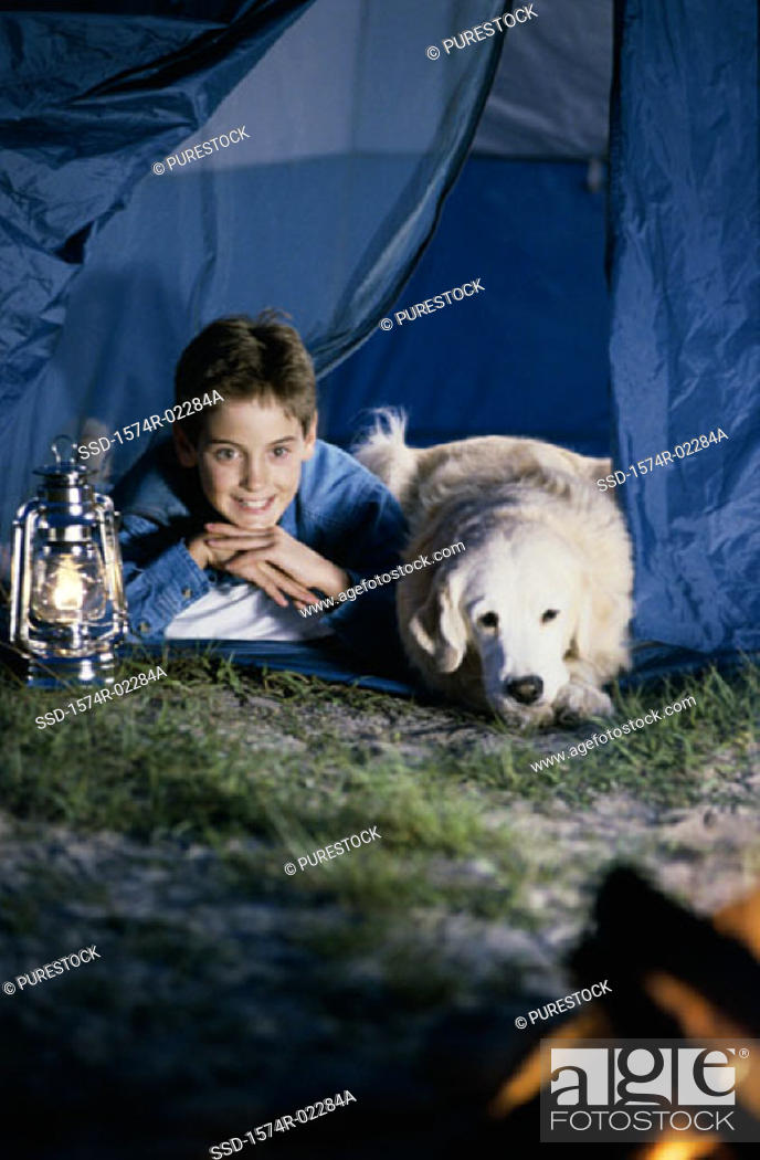 Stock Photo: Boy camping in a tent with his dog.