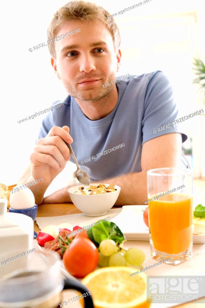 Stock Photo: men eating breakfast cereals.