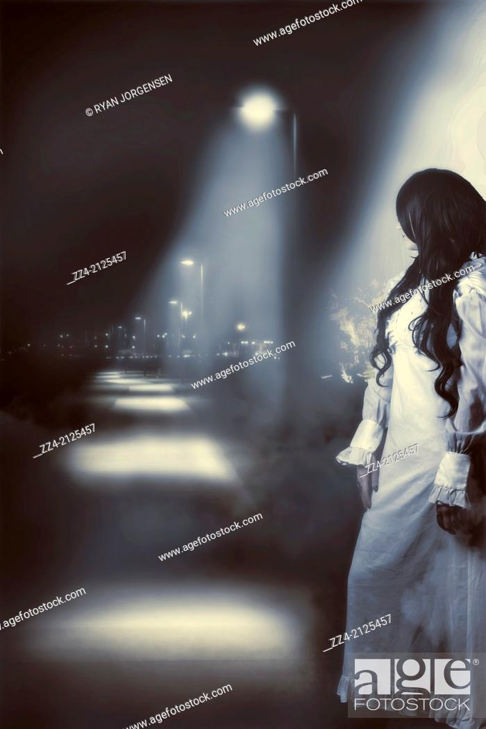 Stock Photo: Back of a sad and lonely woman looking up a foggy path during nightfall. The unknown path of mystery.