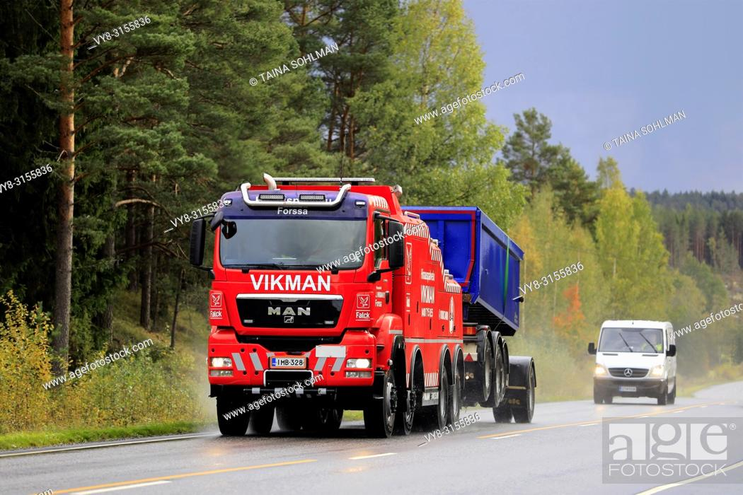 Stock Photo: Salo, Finland. September 28, 2018: Gravel transport trailer being towed by MAN heavy duty tow truck of Hinauspalvelu Vikman along highway on a rainy day.