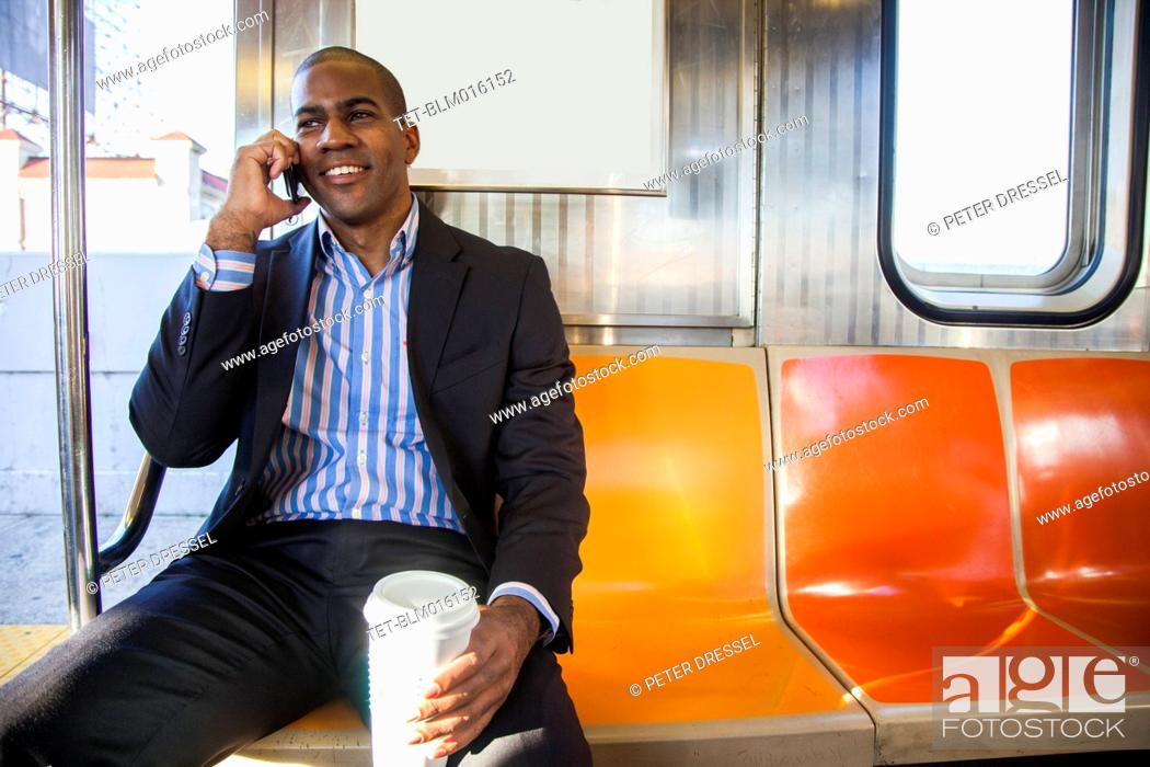 Stock Photo: Black businessman talking on cell phone and riding commuter train.