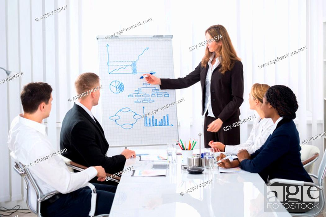 Stock Photo: Group Of Businesspeople Looking At Confident Businesswoman Explaining In Presentation.