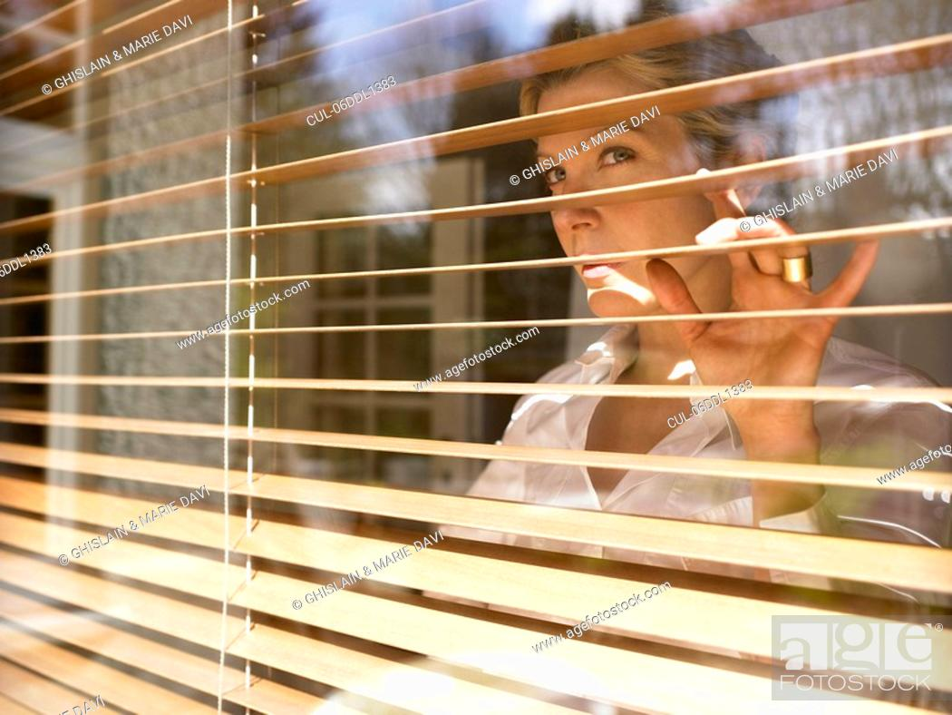 Stock Photo: Woman looking through window.