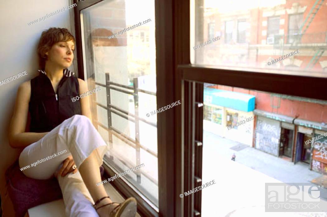 Stock Photo: Woman sitting on windowsill.