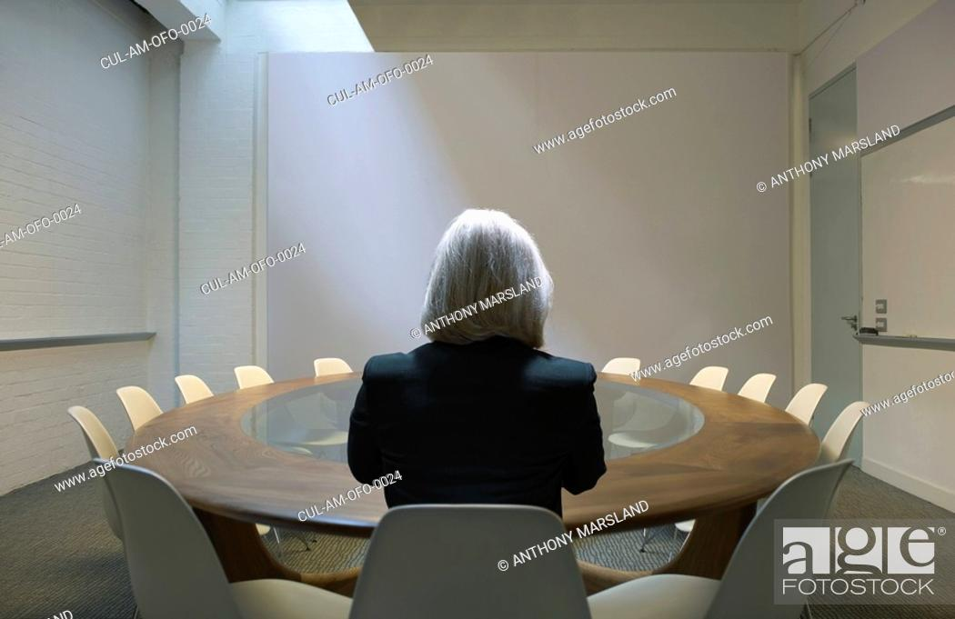 Stock Photo: Woman seated in boardroom from behind.