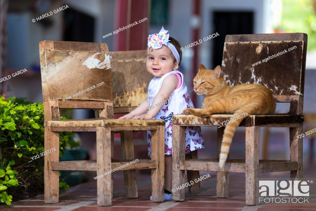 Imagen: Baby girl standing next to chairs playing with a cat.