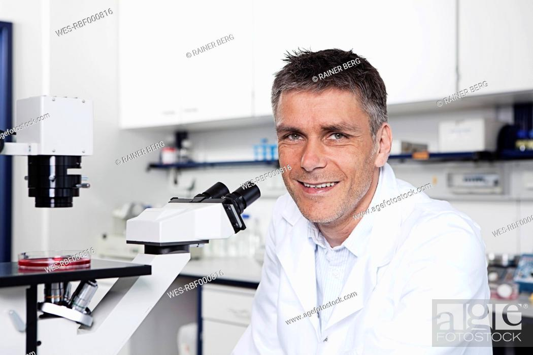 Stock Photo: Germany, Bavaria, Munich, Scientist with microscope in laboratory, portrait.