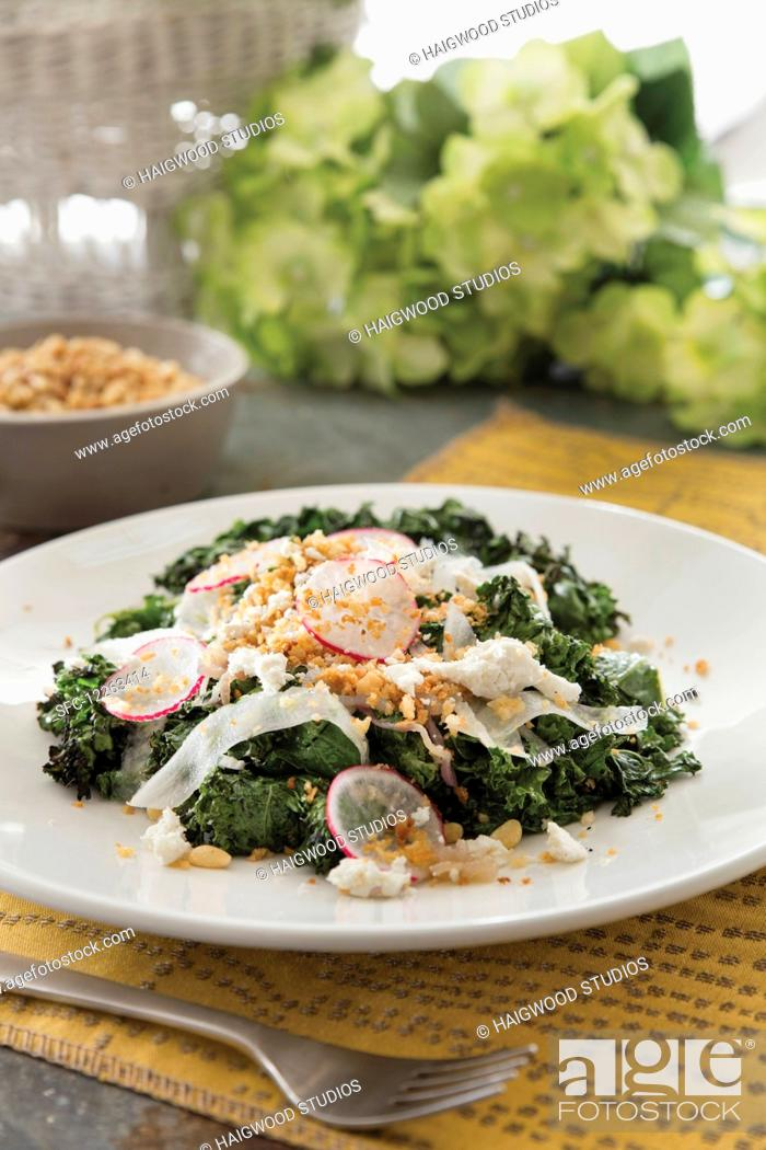 Stock Photo: Grilled kale salad with sliced radish and pine nuts garnish.