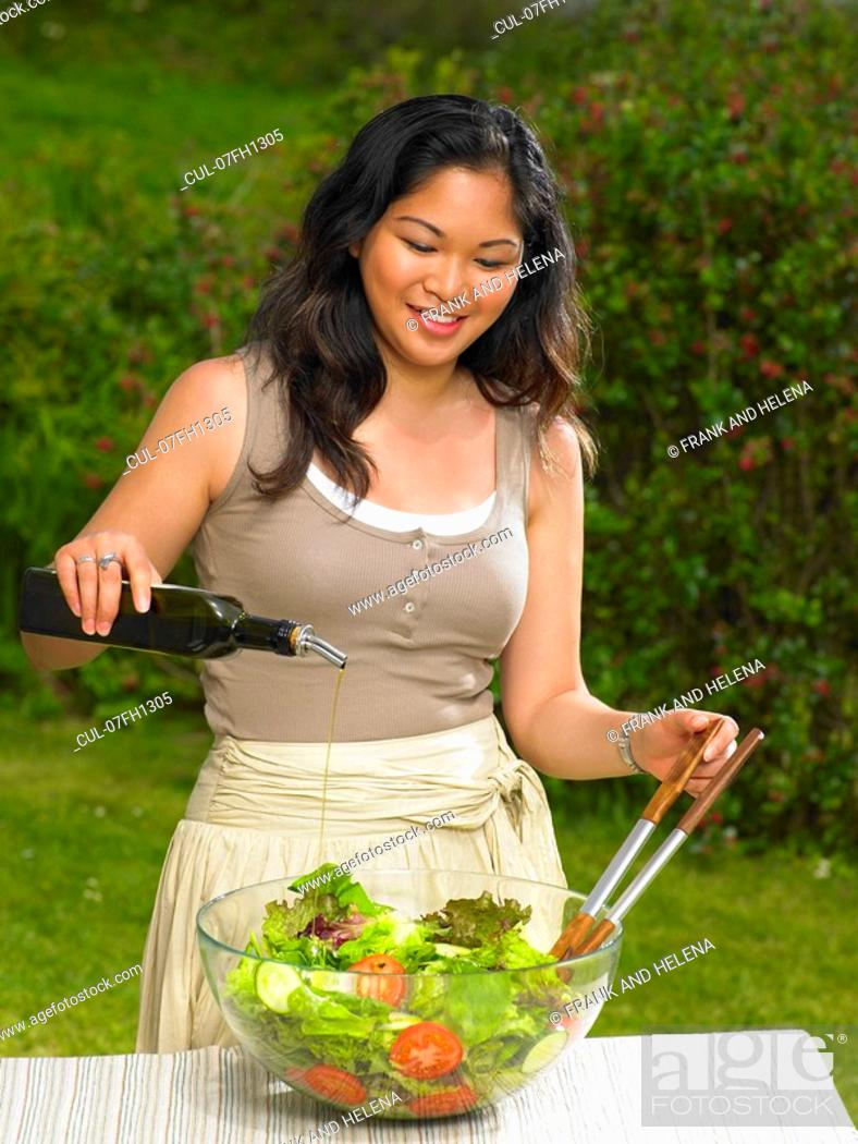 Stock Photo: Young woman pouring olive oil on salad.