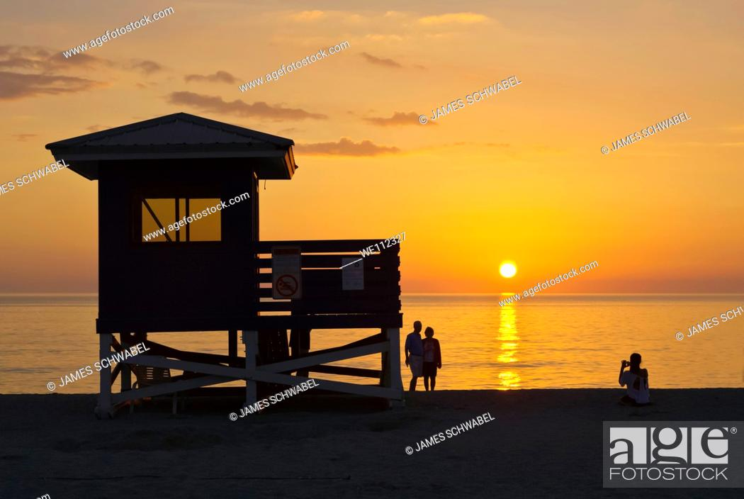 Stock Photo: Life guard stand and people silhouetted aganist orange sunset sky over Gulf of Mexico from Venice Beach Florida.