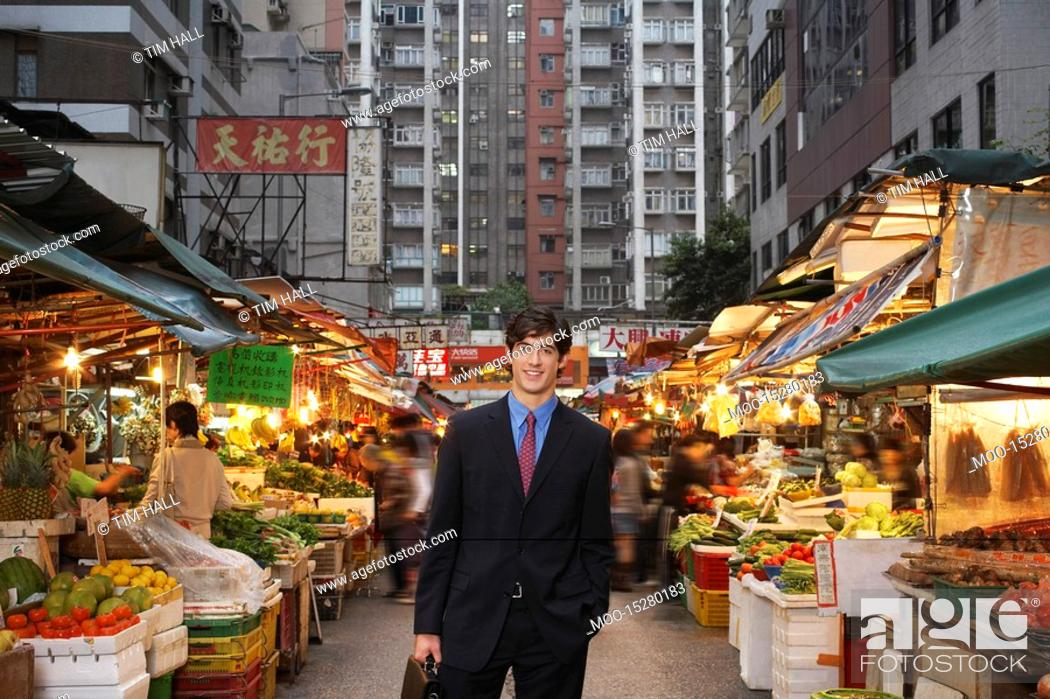 Stock Photo: Portrait of young business man at street market.