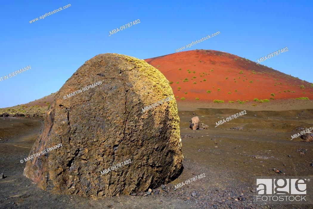 Stock Photo: Lava bomb in front of Caldera Colorada or Montana Colorada, Los Volcanes Natural Park, near Tinajo, Lanzarote, Canary Islands, Spain.