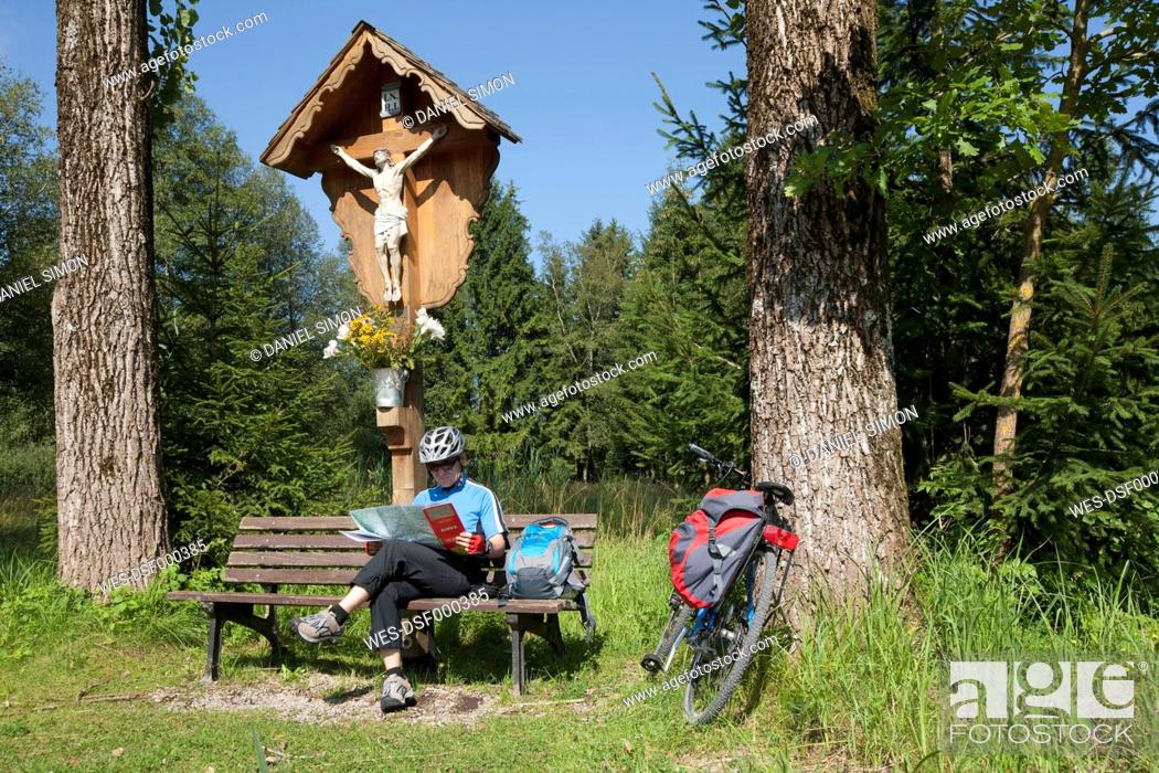 Stock Photo: Germany, Bavaria, Man sitting with map on bench by summit cross.