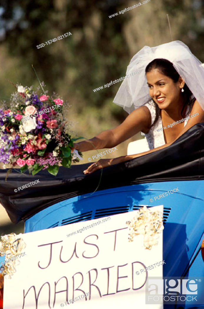 Stock Photo: Bride preparing to toss a bouquet of flowers from a convertible car.