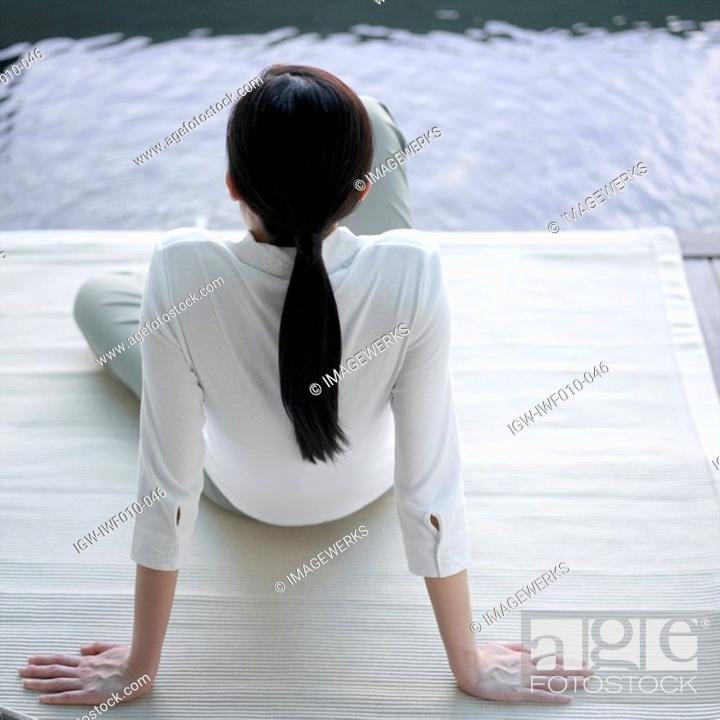 Stock Photo: Rear view of a young woman sitting on the floor.