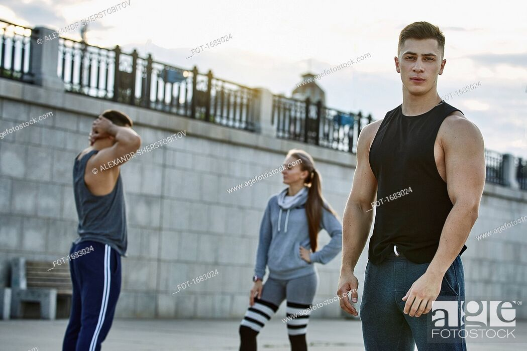 Stock Photo: Portrait of confident young athlete standing with friends against bridge.
