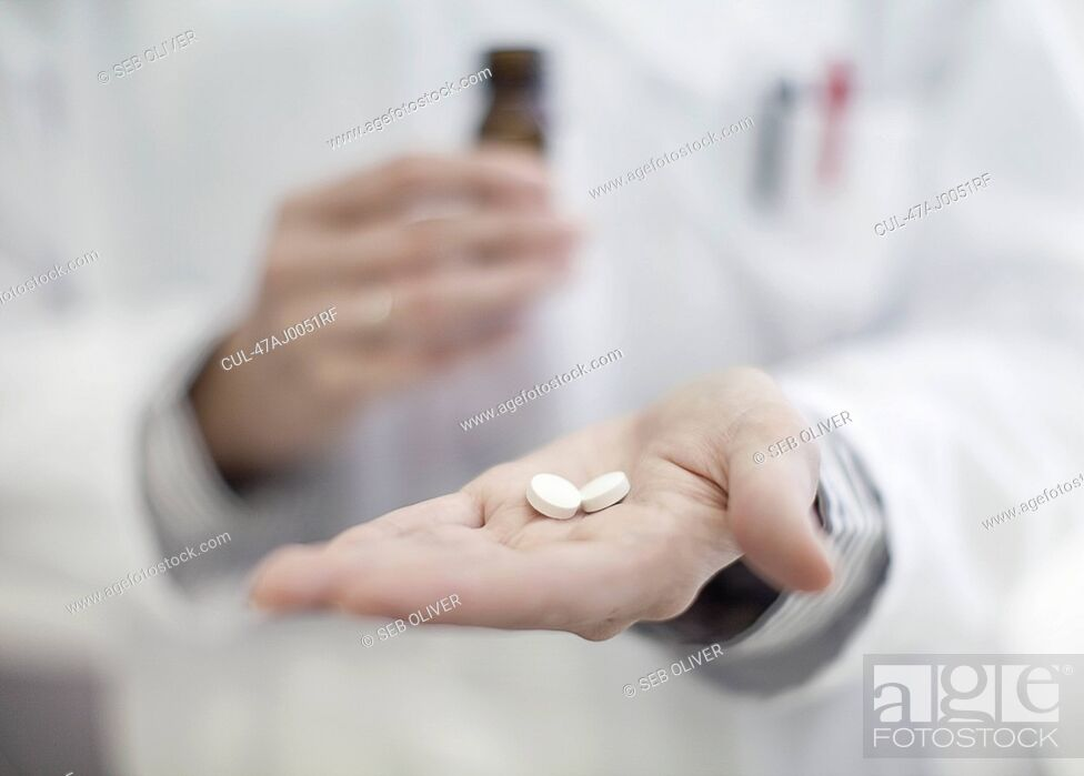 Stock Photo: Close up of doctor holding pills.