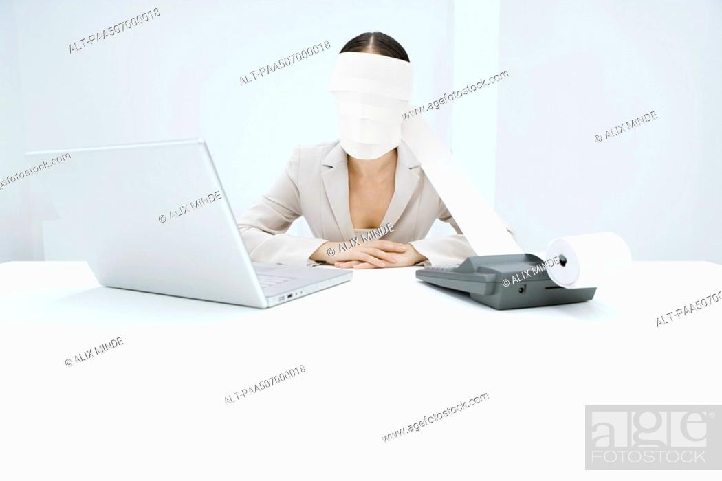 Stock Photo: Woman sitting at desk with adding machine and laptop, printout tape wrapped around head.