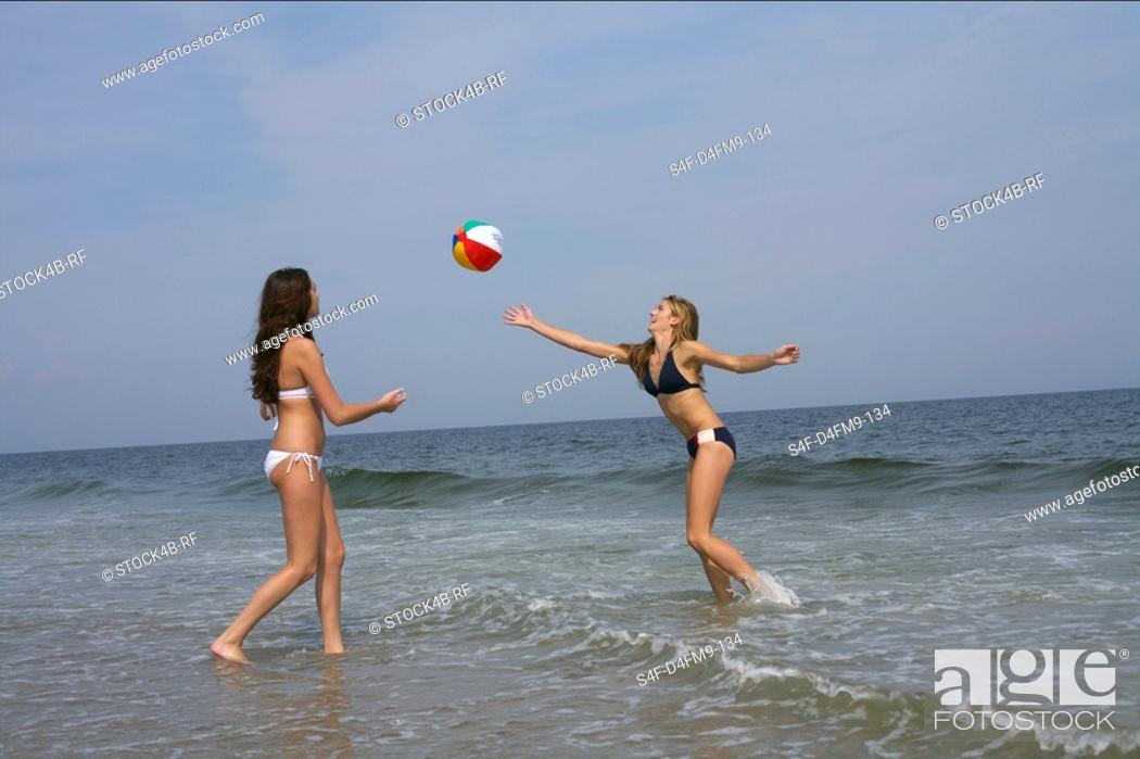 Stock Photo: Two young women playing volleyball at the beach.