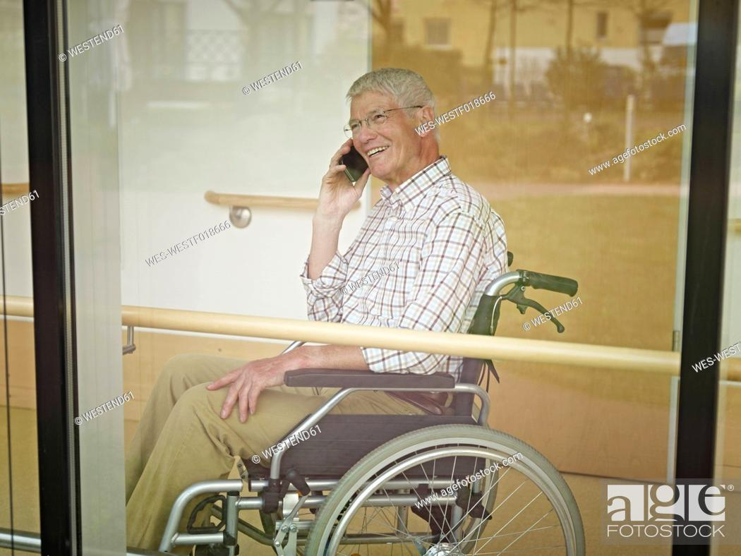 Stock Photo: Germany, Cologne, Senior man on phone in nursing home, smiling.