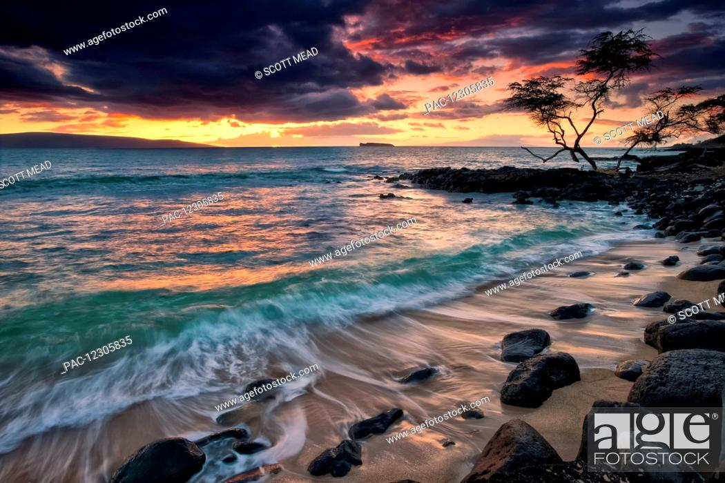 Stock Photo: A dramatic sky at sunset over a turquoise ocean along the coast of a hawaiian island; Hawaii, United States of America.