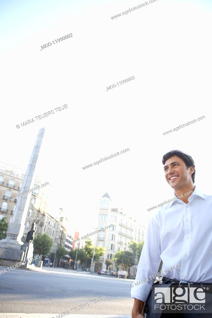 Stock Photo: Businessman on city street holding briefcase by high-rise buildings.