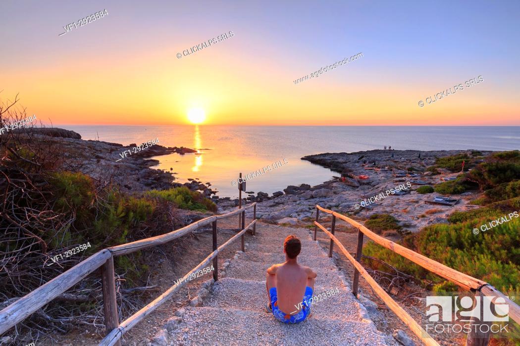 Stock Photo: Tourist watches the sunset at Cala Tramontana, Tremiti Islands, Foggia, Puglia, Italy.