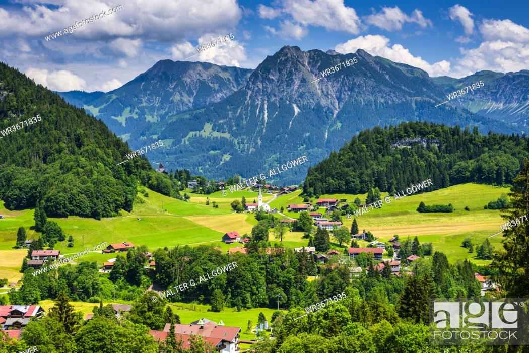 Stock Photo: Germany, Bavaria, Tiefenbach, Countryside village in Allgau Alps with Entschenkopf and Rubihorn in background.