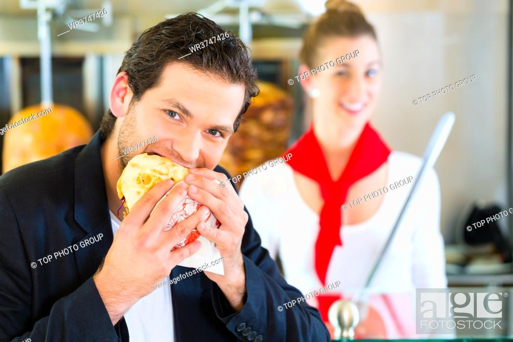 Stock Photo: Doner kebab - friendly vendor and customer in a Turkish fast food eatery, with a freshly made pita bread or kebab in front of skewer.