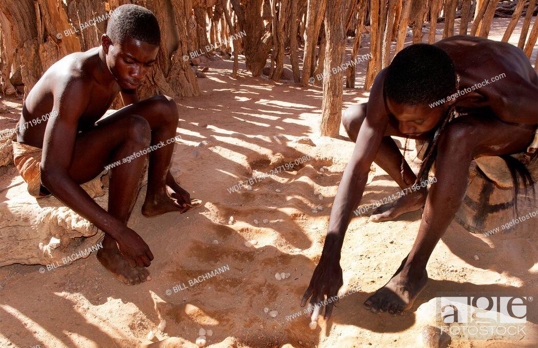 Imagen: Namibia Africa remote Damara Tribe in Damaraland boys playing traditional game called llgus in native village.