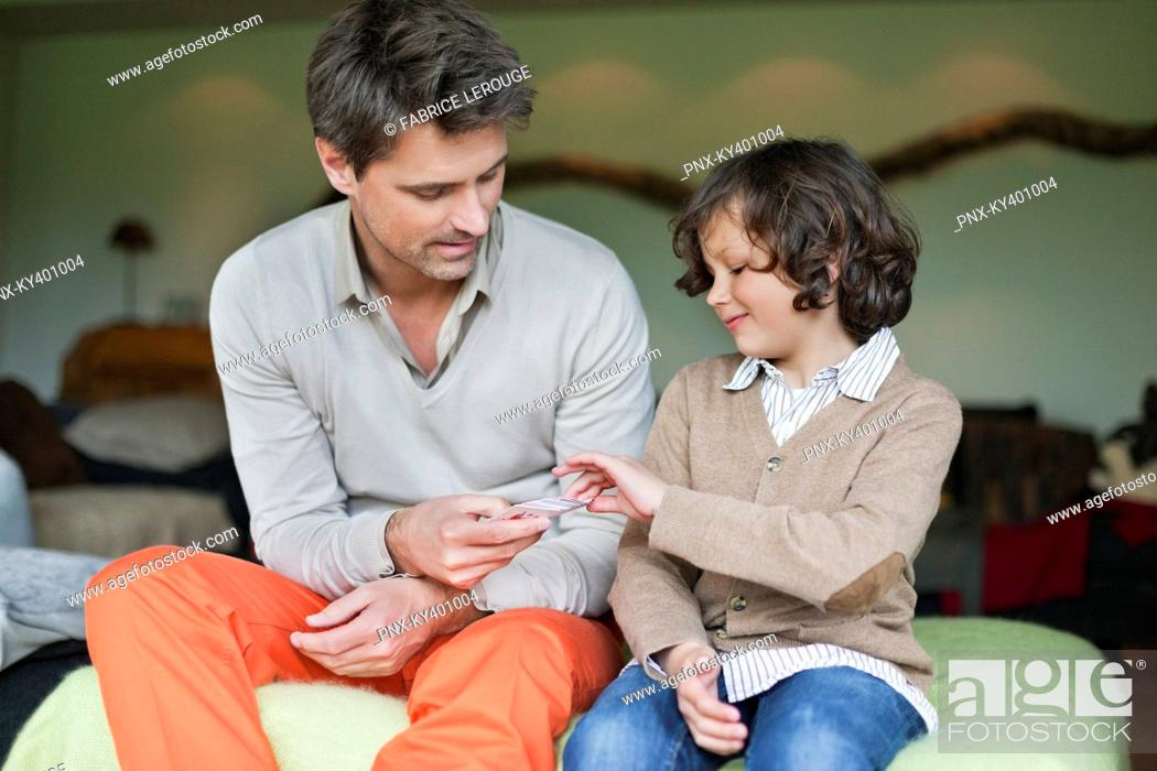 Stock Photo: Man playing cards with his son.
