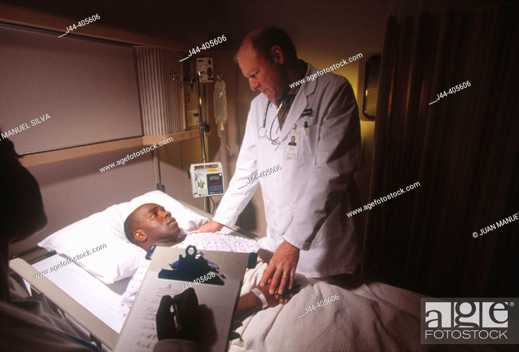 Stock Photo: Doctor and nurse with black man patient in hospital room.