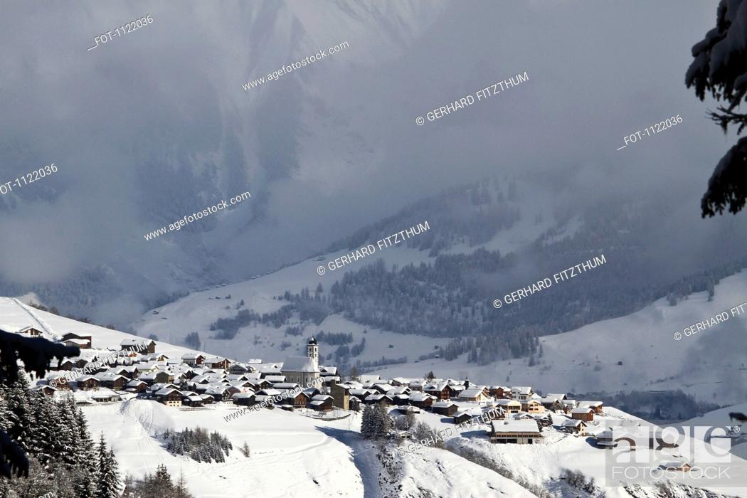 Stock Photo: Snowy village with mountain range and valley in the background.