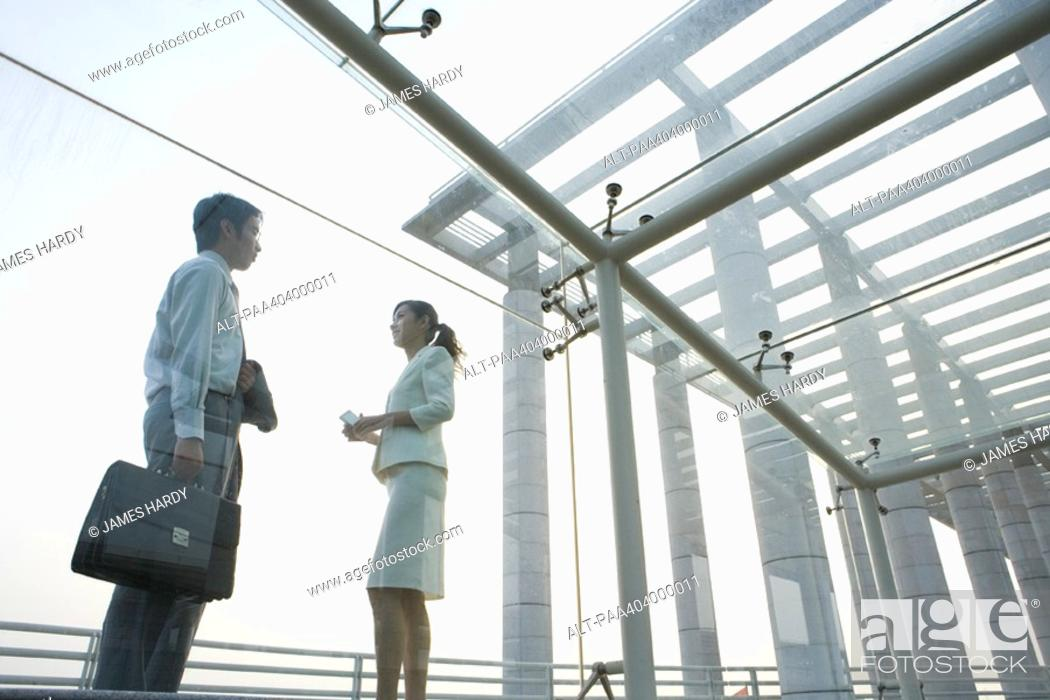 Stock Photo: Young business executives standing under covered walkway, face to face, low angle view.