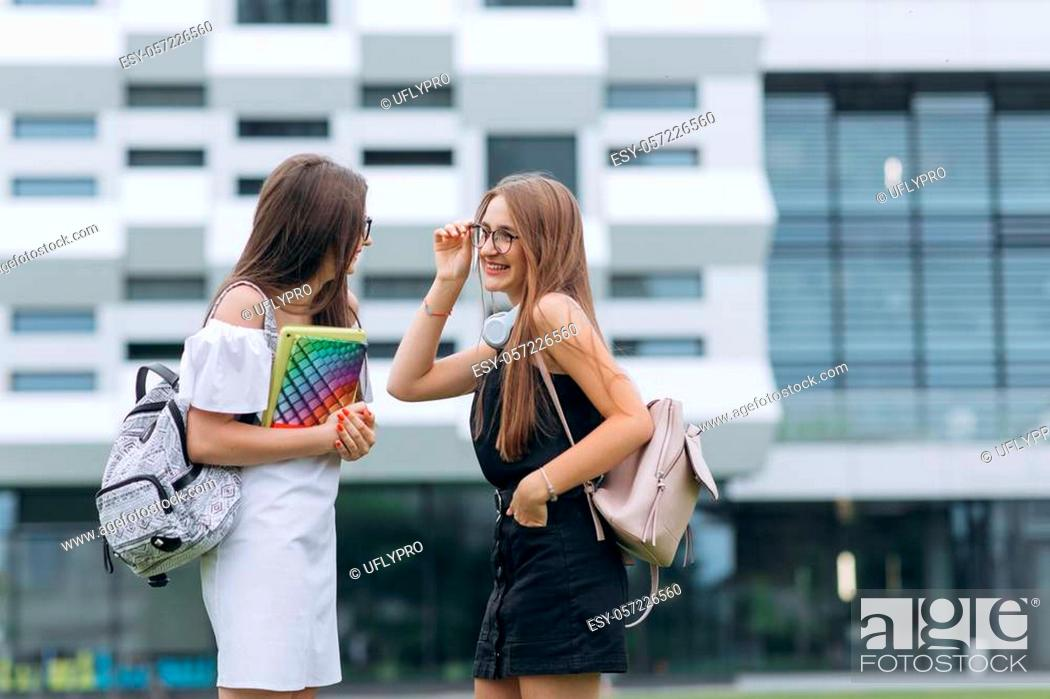 Stock Photo: Two caucasian pretty young female students walking and one girl showing to another some books and where she took them. Portrait shot.