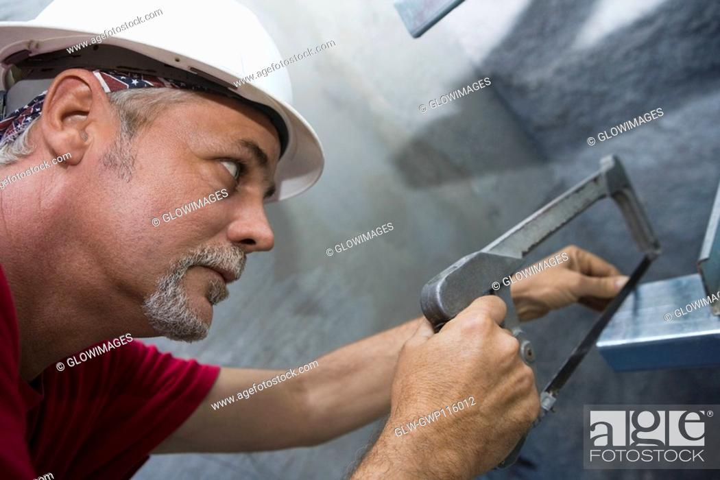 Stock Photo: Close-up of a male construction worker cutting a metal sheet with a saw.