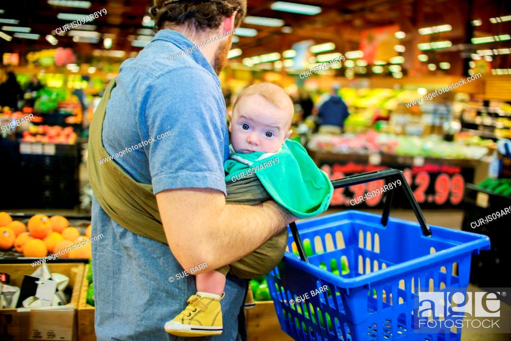 ee75f9f44 Stock Photo - Father holding baby son and shopping basket in supermarket