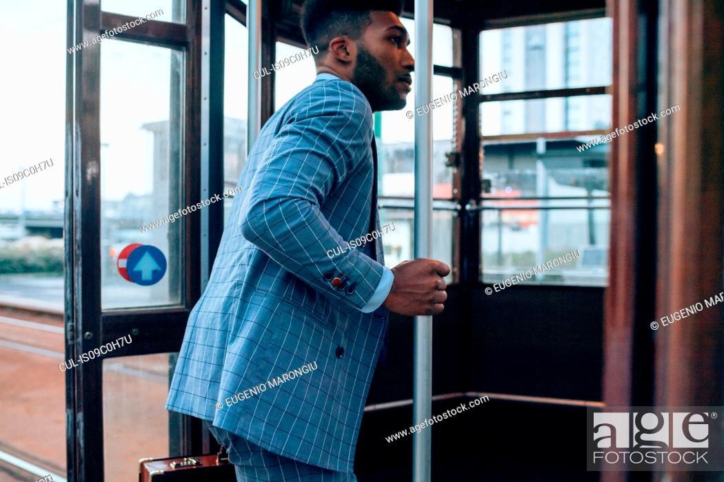 Stock Photo: Businessman boarding tram in city.